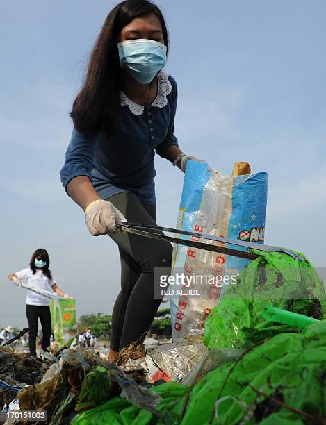 Volunteers remove rubbish washed ashore along the coastline of freedom island in Paranaque City suburban Manila on June 8 2013 during a coastal...