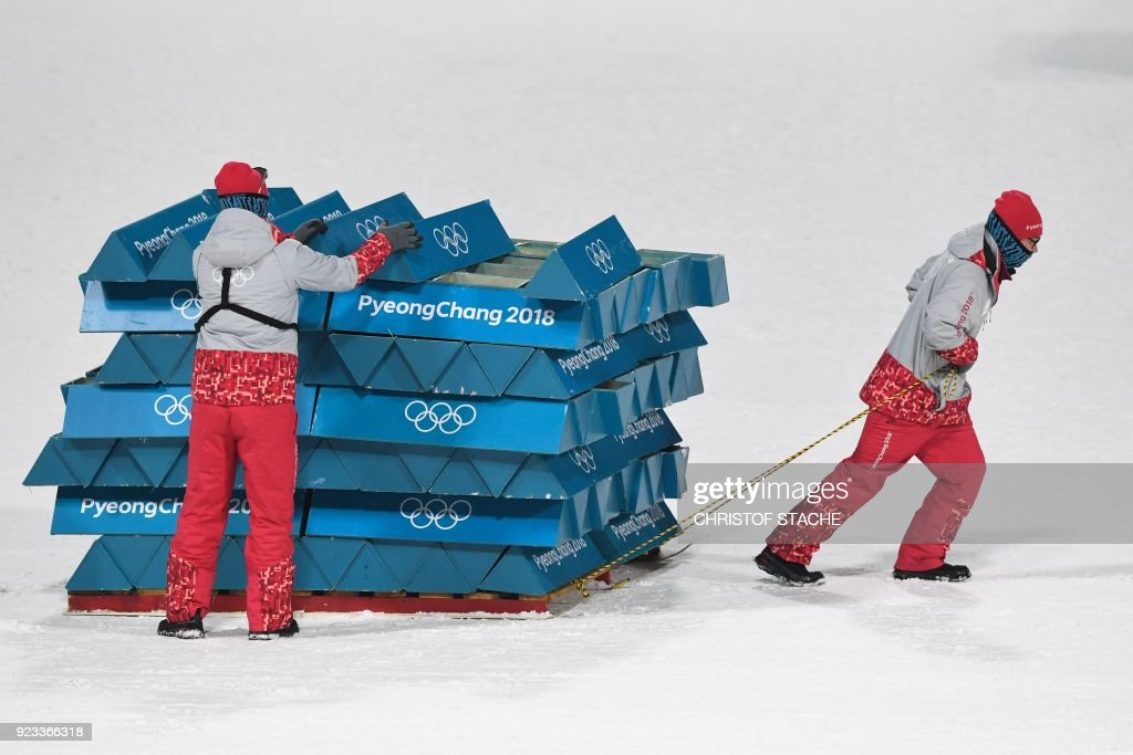 TOPSHOT - Volunteers remove the course markings following the men's 4x7,5km biathlon relay event during the Pyeongchang 2018 Winter Olympic Games on February 23, 2018, in Pyeongchang. / AFP PHOTO / Christof STACHE