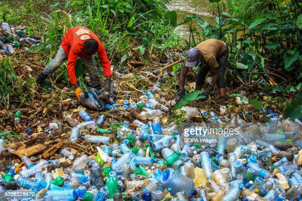 Volunteers removing plastic bottles and other trash polluting Ruaka River An increasing production of singleuse plastics for beverage and other uses...