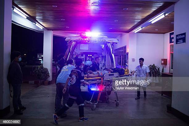 Volunteers rush a severely injured motorbike accident victim to a hospital on December 6 2014 in Vientiane Laos Vientiane Rescue is an allvolunteer...