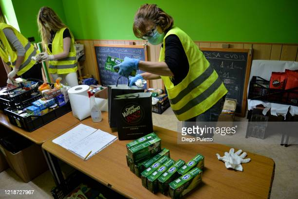 volunteers sanitizes food to give free of charge to people who have financial difficulties caused by COVID19 on April 14 2020 in Candiolo near Turin...