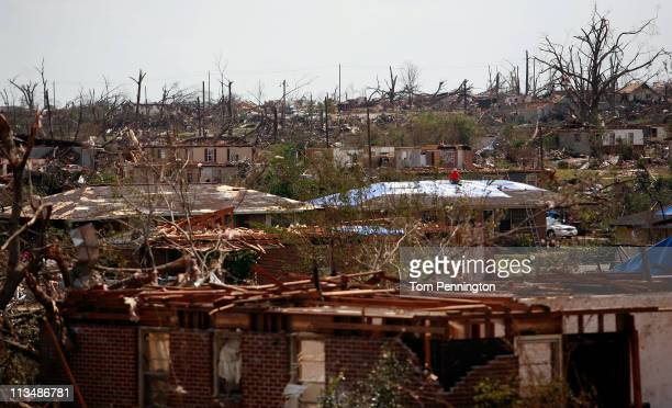 Volunteers secure a blue tarp to a damaged house on May 2 2011 in Holt Alabama Alabama the hardesthit of six states is reported to have been battered...