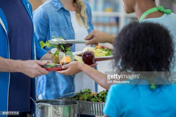 Volunteers serve healthy meal in soup kitchen