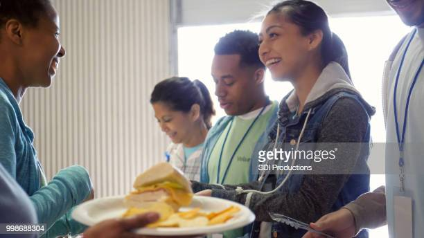 volunteers serve healthy meal to the homeless - humanitarian aid stock pictures, royalty-free photos & images