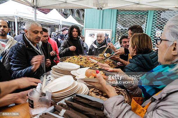 Volunteers serve paella to people on December 25 in Bordeaux southwestern France during a Christmas event organised by the local restaurant Bodega...