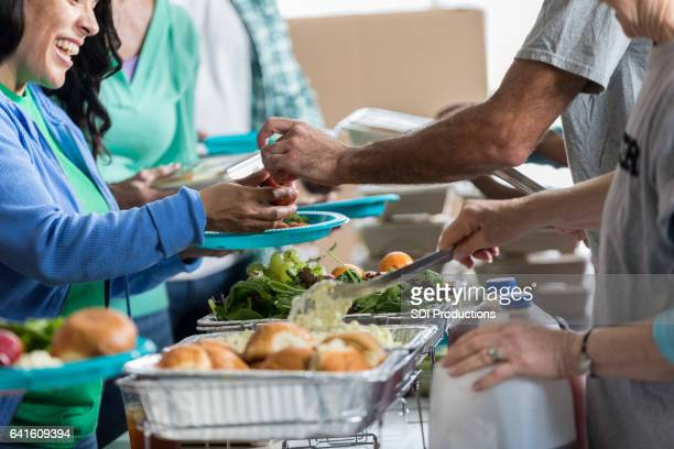volunteers serve people in soup kitchen - benefits stock pictures, royalty-free photos & images