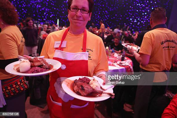 Volunteers serve plates of Christmas goose at the 22nd Franz Zander Christmas Evening for the Homeless at the Estrel Hotel on December 19 2016 in...