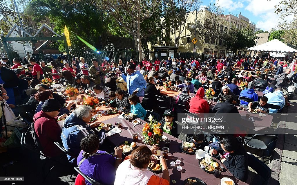 Volunteers serve Thanksgiving lunch to homeless outside the Los Angeles Mission in the city's Skid Row during the annual event in Los Angeles, California, on November 25, 2015. LA is home to the nation's largest population of chronically homeless people in the country, where nearly all sleep on the streets, according to figures released on November 19, 2015 by the U.S. Housing and Urban Development Department.