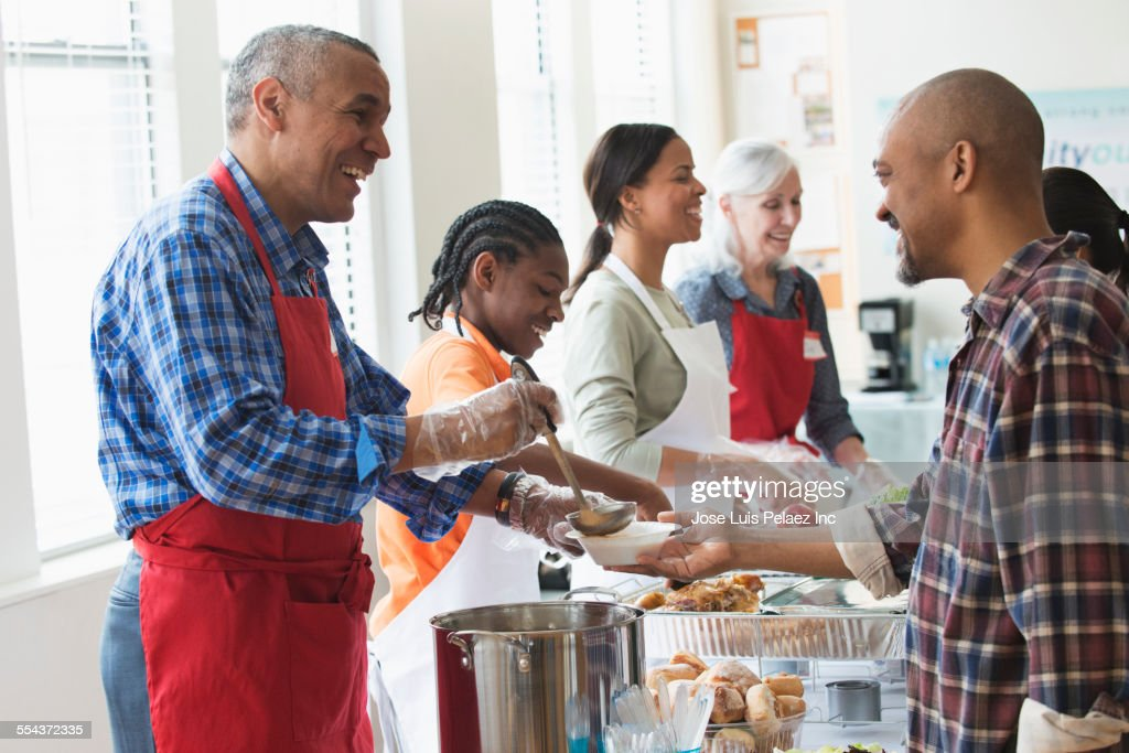 Volunteers serving food at community kitchen : Stock Photo