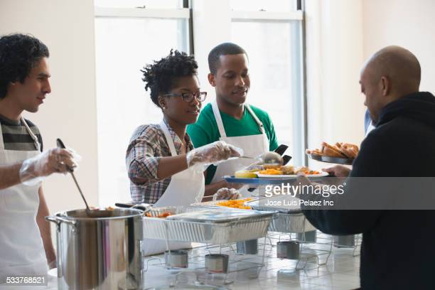 volunteers serving food in cafeteria - black glove stock pictures, royalty-free photos & images