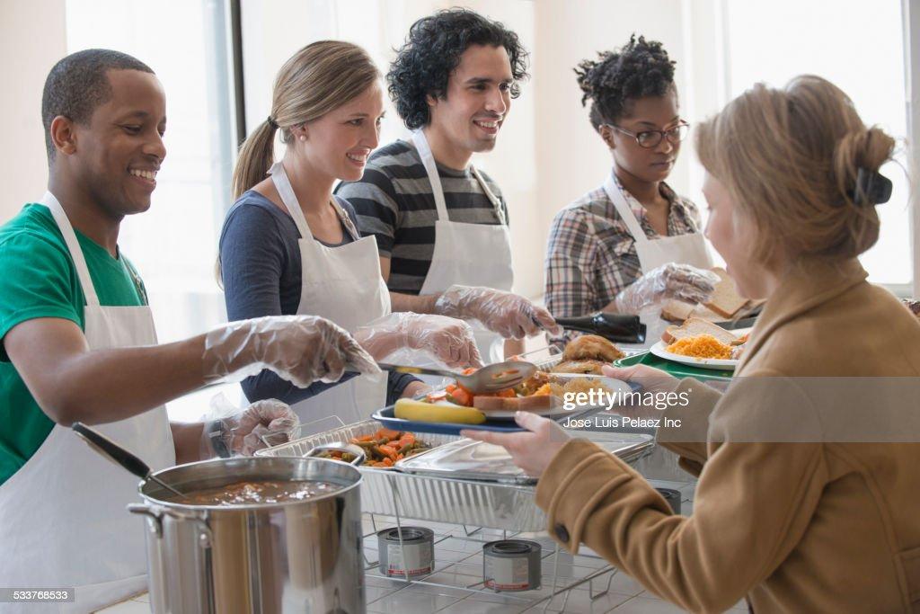 Volunteers serving food in cafeteria : Foto stock