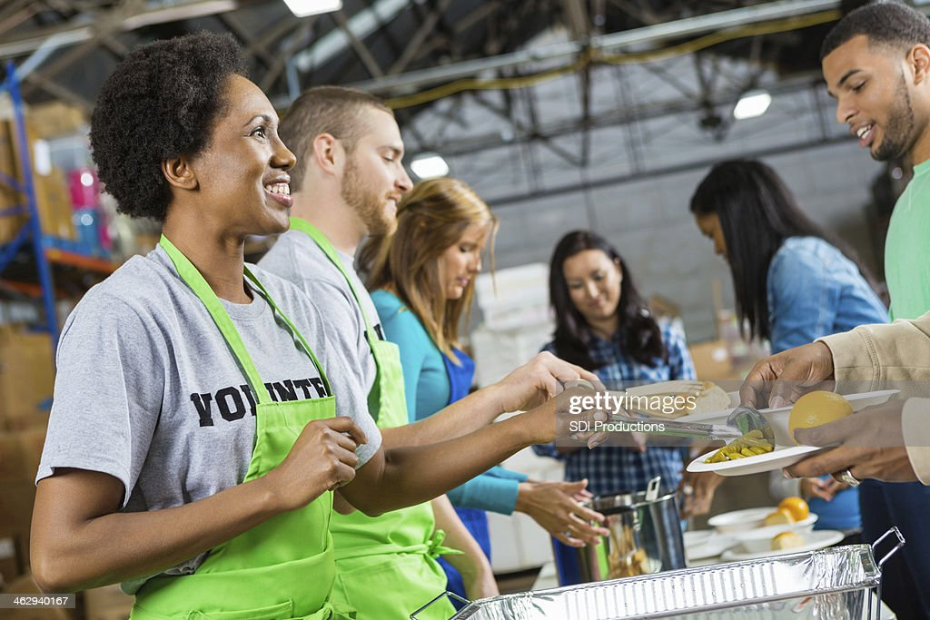 Volunteers serving healthy hot meal at soup kitchen : Stock Photo