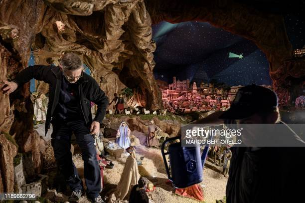 Volunteers set nativity figures at the 43rd edition of the Presepio of Cavallermaggiore a 300sqm Christmas Nativity crib in the Oratorio San Michele...