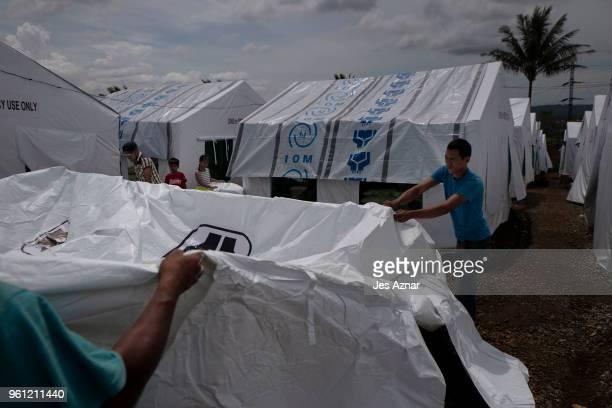 Volunteers setup a tent for incoming displaced families to occupy inside the Sarimanok tent cityon May 16 2018 in Marawi Philippines With their homes...