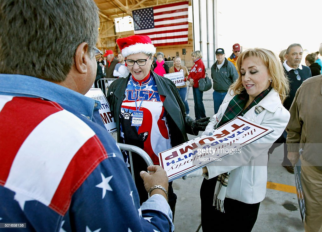 Volunteers Sharon Gray (C) and Julie Fisher (R) hand out Trump rally signs during Republican presidential candidate Donald Trump's campaign event at the International Air Response facility on December 16, 2015 in Mesa, Arizona. Trump is in Arizona the day after the Republican Presidential Debate hosted by CNN in Las Vegas, Nevada.