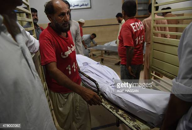 EDHI volunteers shift dead bodies of heatwave victims at the EDHI morgue in Karachi on June 21 2015 A heatwave has killed at least 45 people in...