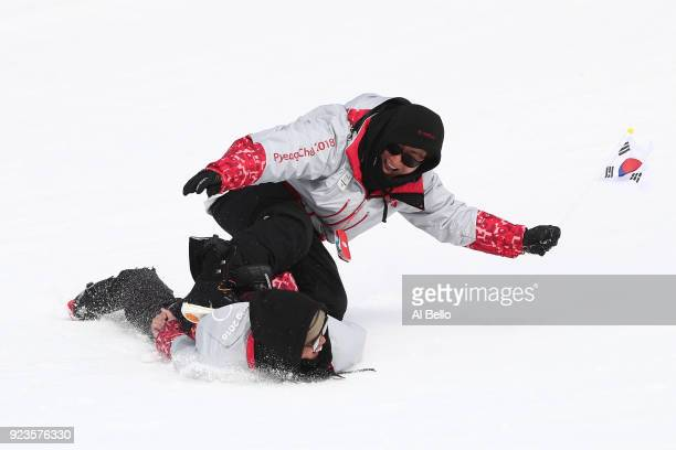 Volunteers slide down the slope after the Men's Big Air Final on day 15 of the PyeongChang 2018 Winter Olympic Games at Alpensia Ski Jumping Centre...