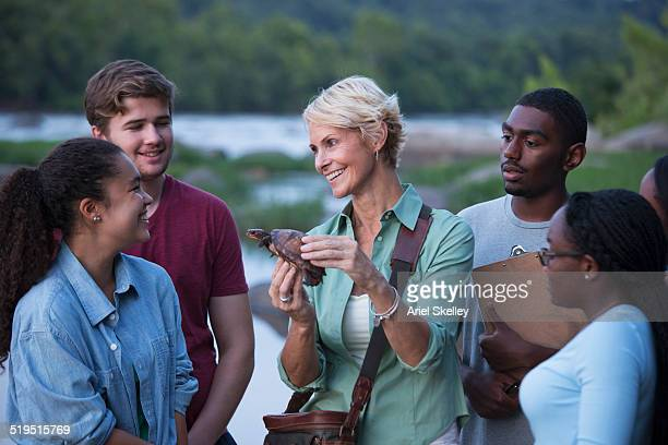 Volunteers smiling and holding turtle in river