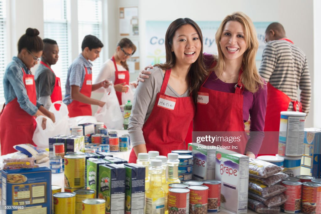 Volunteers smiling near canned goods at food drive : Foto stock