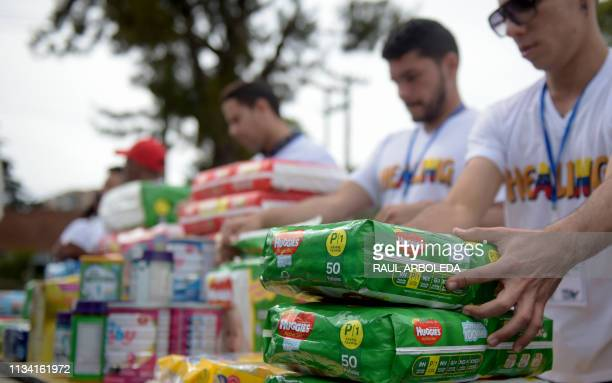 Volunteers sort donations during the Healing event to collect aid food and supplies for Venezuelans affected by the crisis in Bogota on March 31 2019