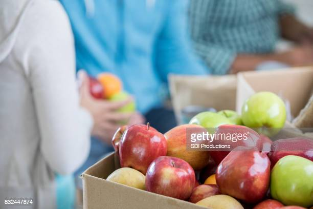 volunteers sort fresh fruit during food drive - food bank stock pictures, royalty-free photos & images