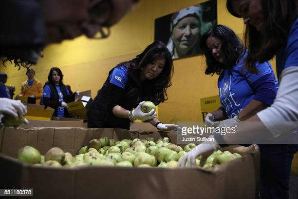 Volunteers sort pears at the SFMarin Food Bank on November 28 2017 in San Francisco California A day after consumers spent billions of dollars on...