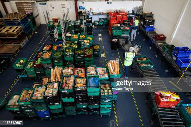 Volunteers sort though crates of surplus food collected from supermarkets at foodwaste charity The Felix Project's warehouse in Park Royal on...