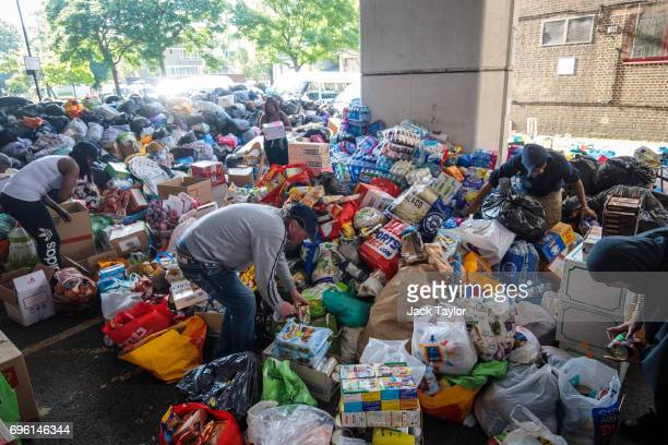 Volunteers sort through a pile of food and clothes donations near to the site of the Grenfell Tower fire on June 15 2017 in London England At least...