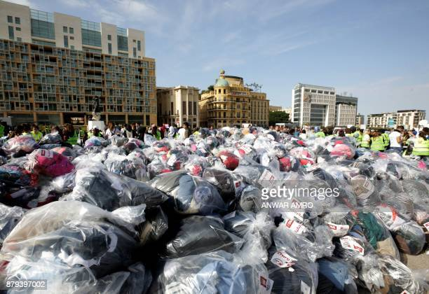 Volunteers sort through aid consisting of winter clothing blankets heaters and other necessities in the capital Beirut's Martyrs Square on November...