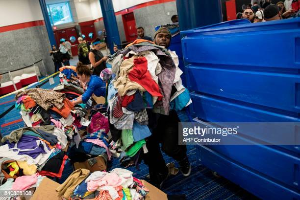 Volunteers sort through donated clothing at a shelter in the George R Brown Convention Center during the aftermath of Hurricane Harvey on August 28...