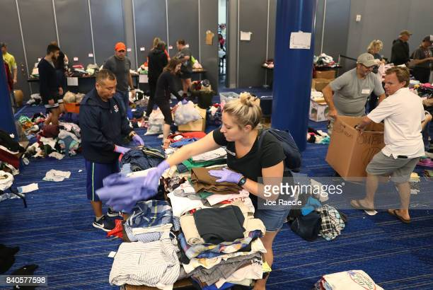 Volunteers sort through donated clothing for the people that have taken shelter at the George R Brown Convention Center after flood waters from...