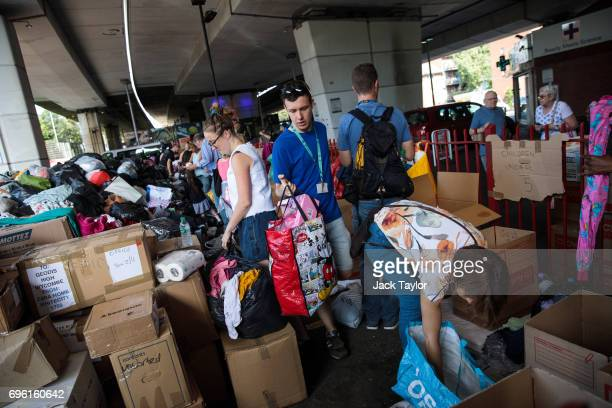 Volunteers sort through donations for victims near to the site of the Grenfell Tower fire on June 15 2017 in London England At least twelve people...