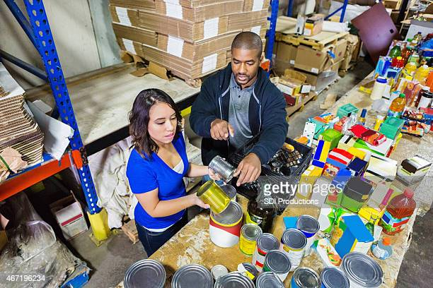 volunteers sorting donations in large food bank distribution warehouse - humanitarian aid stock pictures, royalty-free photos & images