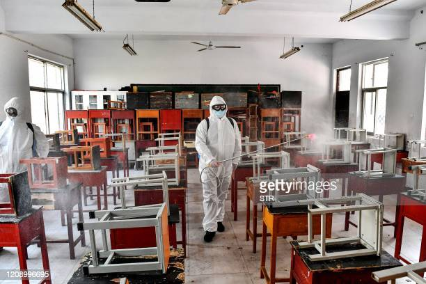 Volunteers spray disinfectant at a classroom as the school prepares for students returning after the term opening was delayed due to the COVID-19...