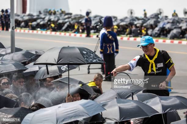 Volunteers spray mourners with cooling water as they wait on the street near the Royal Crematorium at Sanam Luang ceremonial ground ahead of the...