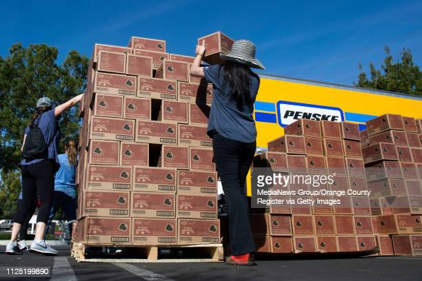 Volunteers stack Girl Scout Smores as a moving truck loads up cookies during the Girl Scout Cookie Mega Drop at the Anaheim Business Complex in...