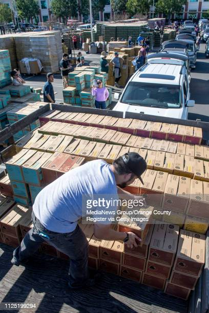Volunteers stack Girl Scout Smores in the back of a truck for Fullerton/La Habra Troop 2662 as a line of cars load up during the Girl Scout Cookie...