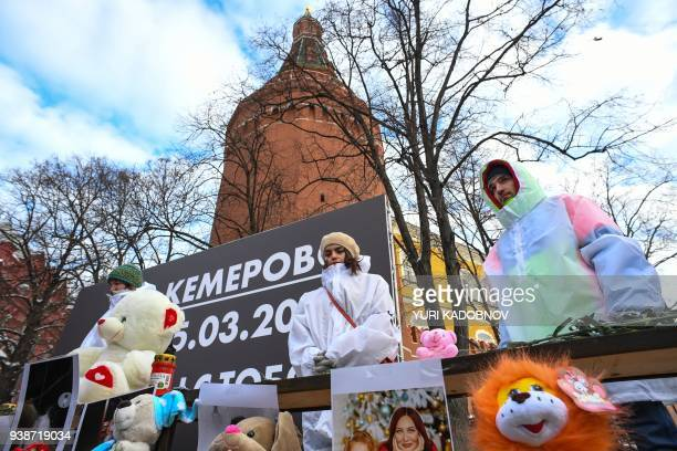 Volunteers stand by a makeshift memorial in tribute to the victims of a Siberian shopping mall fire at Manezhnaya Square in downtown Moscow on March...