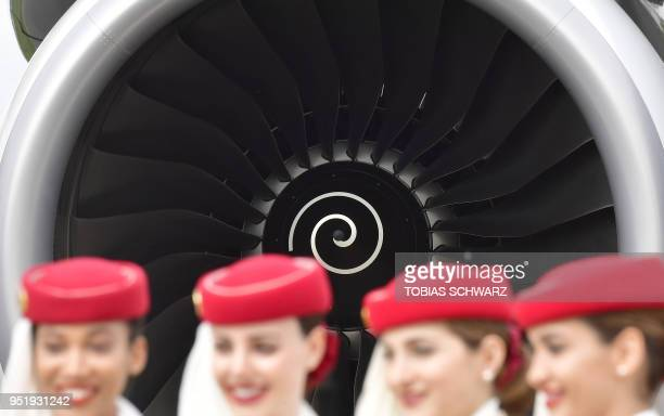 Volunteers stand next to an engine of an Airbus A380800 at the International Aerospace Exhibition in Berlin Schoenefeld on April 27 2018 According to...