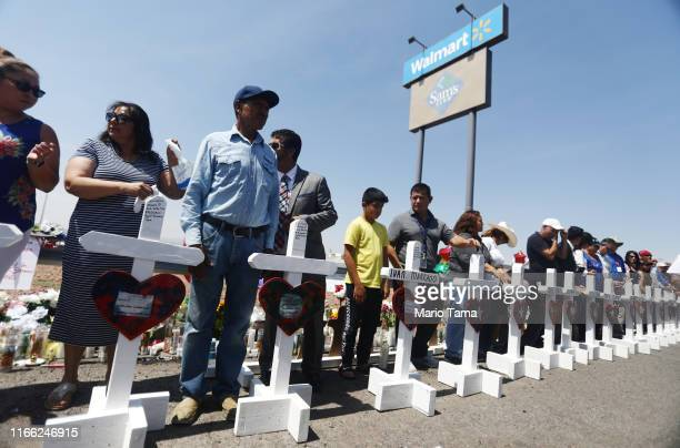 Volunteers stand with handmade crosses memorializing the victims of a mass shooting at a makeshift memorial outside Walmart where the shooting took...