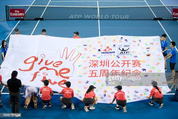Volunteers stretch out a banner during the Shenzhen Open 5th anniversary celebration during the 2018 ATP Shenzhen Open on September 27, 2018 in...