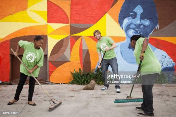 Volunteers sweeping ground