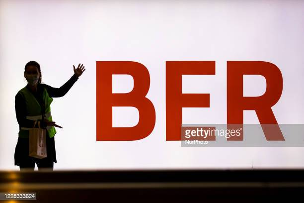Volunteers take a picture in front of the logo BER of Berlin Brandenburg Airport 'Willy Brandt' during a test run head of its opening, planned for...