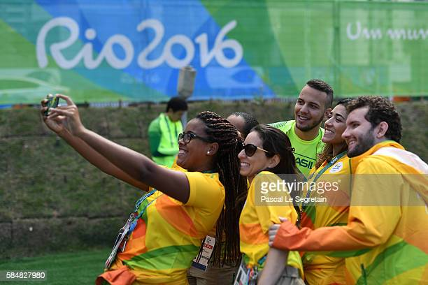Volunteers take a selfie during Brazilian team for the 2016 Rio Olympics official welcome and flag raising ceremony in the Athletes Village on July...
