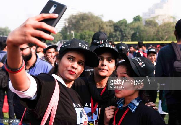 Volunteers take selfies during an event to mark International Condom Day in New Delhi on February 13, 2018. The event was organised by AIDS...