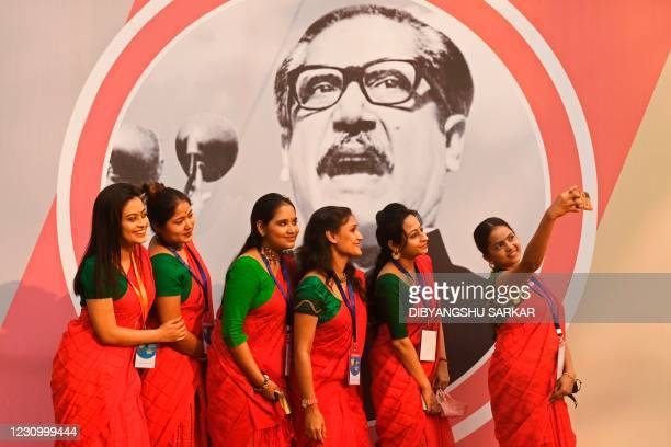 Volunteers take their selfie in front of a picture of Bangladeshs founder Sheikh Mujibur Rahman, during a function organised to commemorate the...