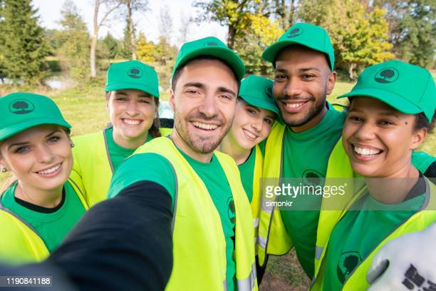 volunteers taking selfie in park - mid adult stock pictures, royalty-free photos & images