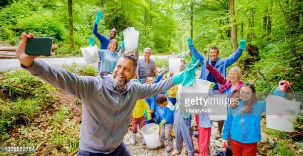 smiling volunteers gesturing while taking selfie