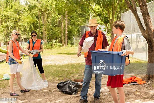 Volunteers: Teenage boy carries bin for fellow recyclers. Environmental Conservation