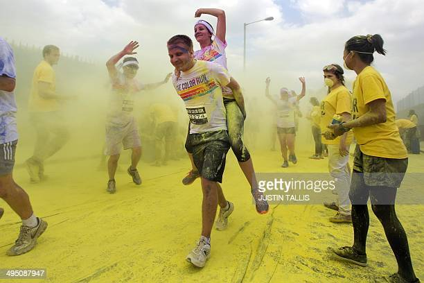 Volunteers throw colourful powder on a participants taking part in the Colour Run around Wembley Stadium in London on June 1 2014 AFP PHOTO / JUSTIN...